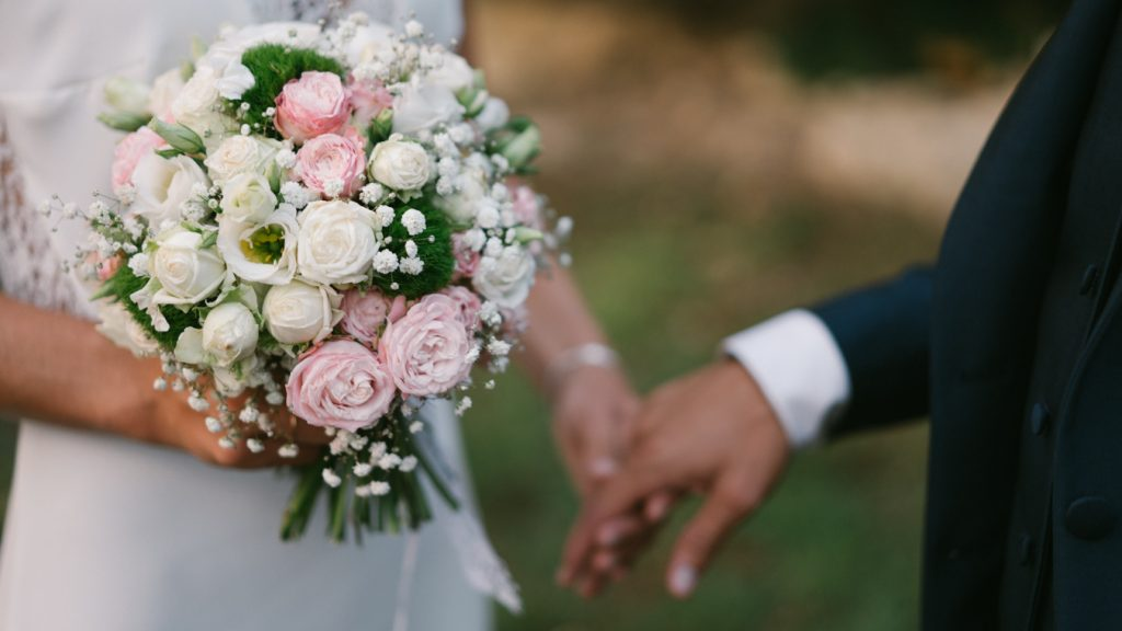 Mariés se tenant main avec bouquet de mariée